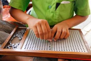 Alumno escribiendo en braille